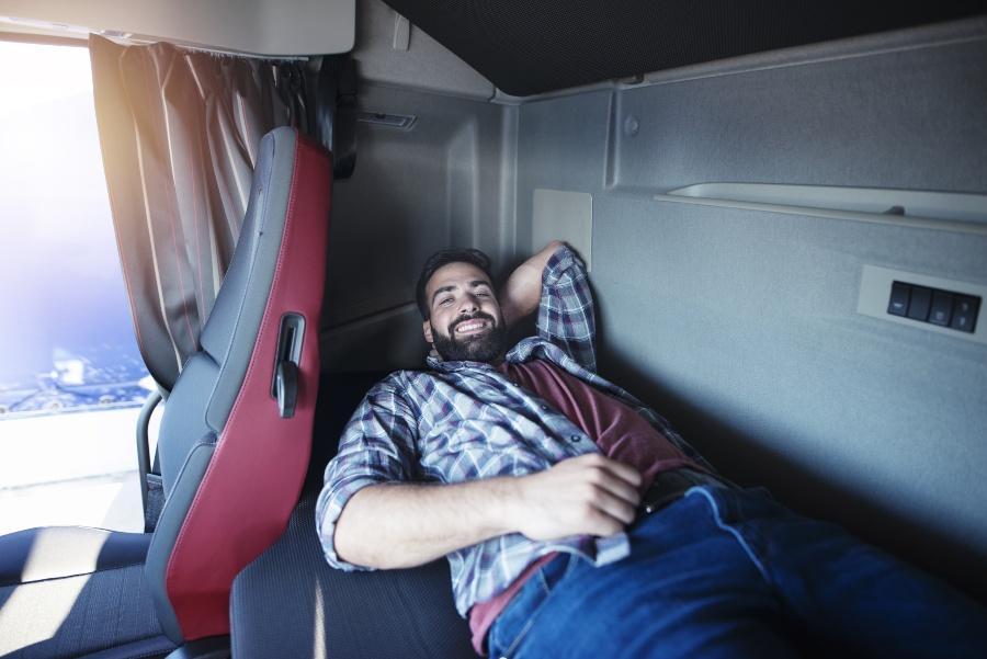 Junger Mann liegt im LKW in einer Schlafkabine - LKW-Matratzen