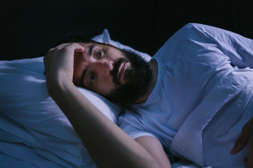 Mann liegt im Bett, kann nicht schlafen