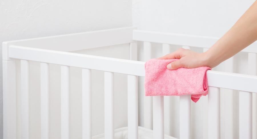 Jemand reinigt Kinderbett mit Tuch -Holzreinigung
