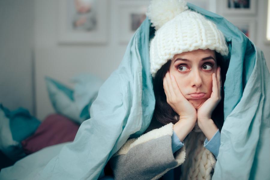 Junge Frau liegt unzufrieden mit Mütze im Bett