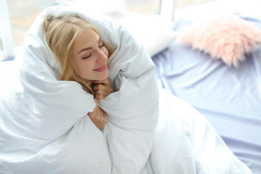 Junge Frau in Decke eingekuschelt - Schlafzimmer zu kalt oder zu warm