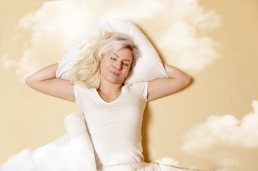 Junge Frau schläft wie auf Wolken -