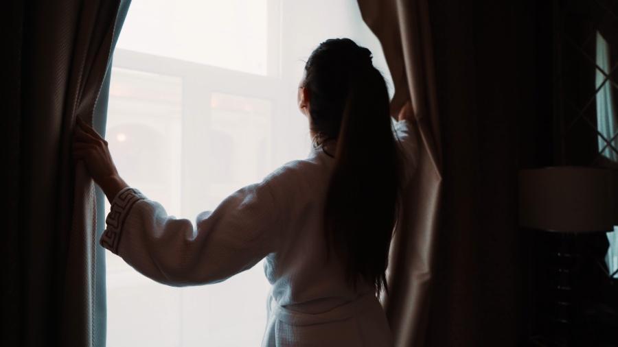 Junge Frau steht morgens vor ihrem Fenster - Schlafzimmer zu kalt oder zu warm