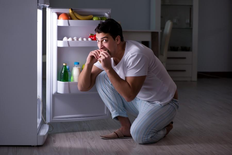Junger Mann isst nachts am Kühlschrank - Schlafmangel und Übergewicht