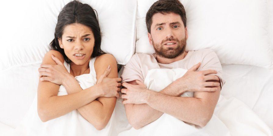 Junges Paar im Bett - Schlafzimmer zu kalt oder zu warm