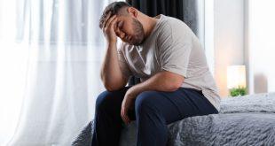 Übergewichtiger Mann im Bett - Schlafmangel und Übergewicht